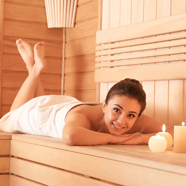 Young woman lying on wooden bench in sauna