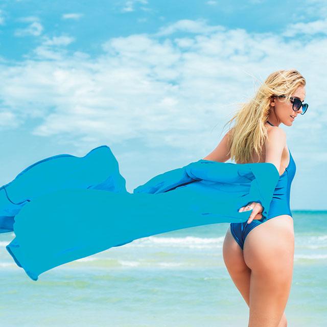 Junge Dame mit Sonnenbrille und Badeanzug am Strand