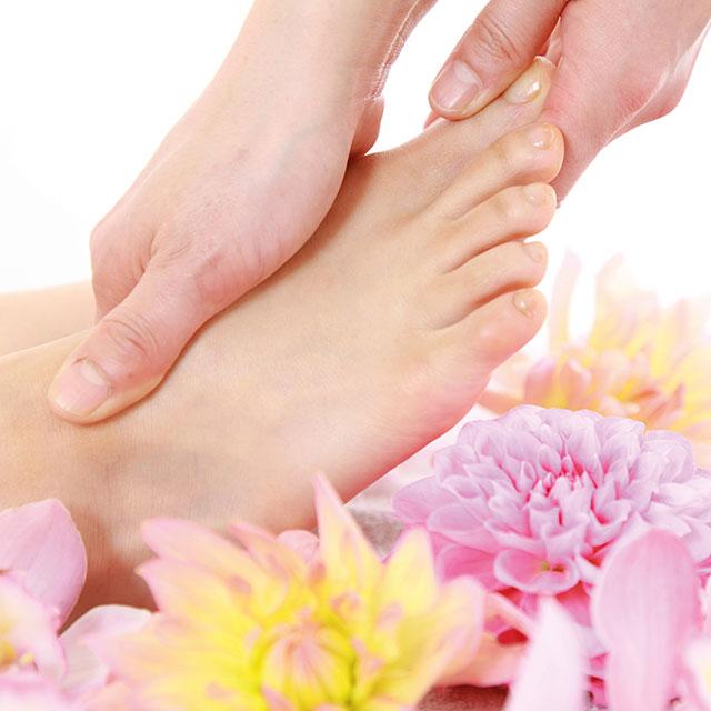 Hände Massieren Füße bei der Fussreflexzonenmassage mit Blumen