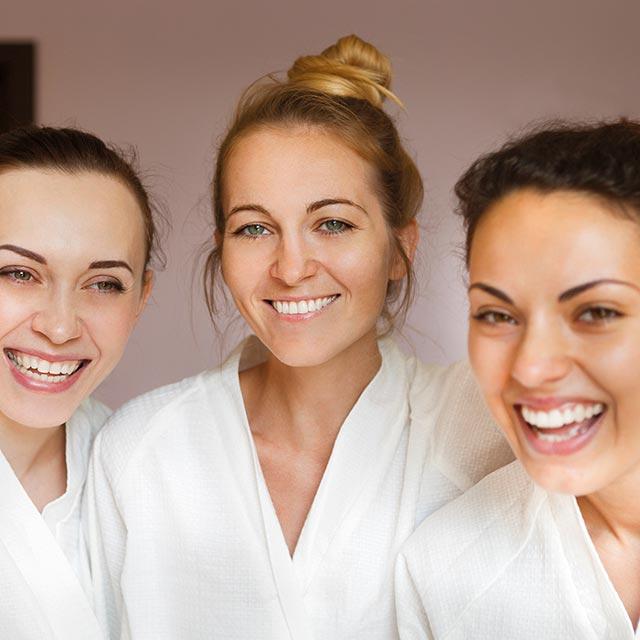 drei fröhliche Mädchen im Bademantel